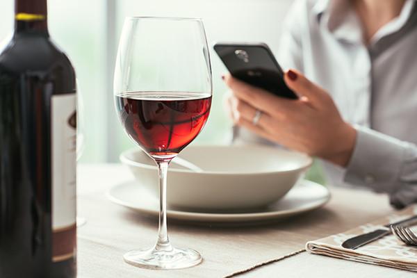 mesa com mão segurando uma taça de vinho